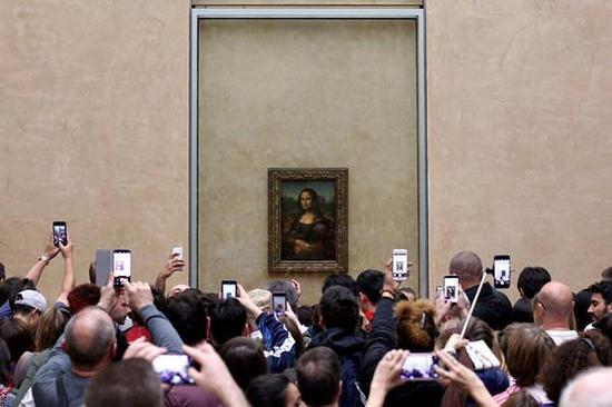 法国卢浮宫《蒙娜丽莎》前举着手机拍摄的观众