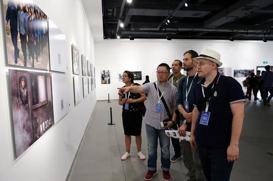 参展摄影家兴致勃勃地观看展览