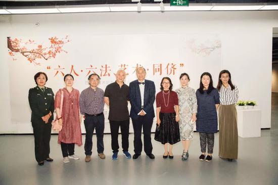 开幕式现场,出席嘉宾与参展艺术家合影