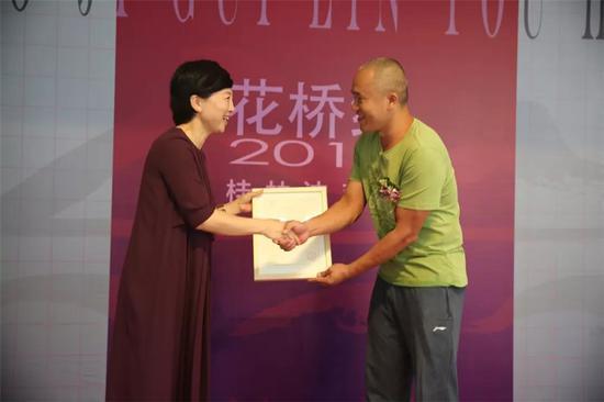 桂林市花桥美术馆馆长邱丽萍向参展艺术家代表谢宗波颁发收藏证书