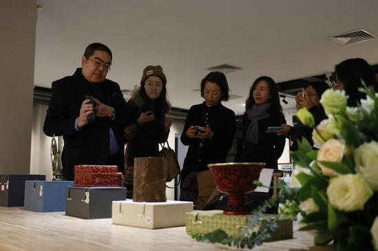北京湛然拍卖副总经理朱邈(左一)介绍拍品
