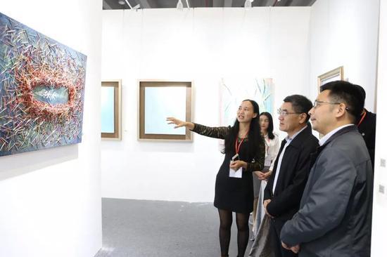 南方文交所朱雀云负责人唐有元为为观展领导介绍展位当代画家作品。