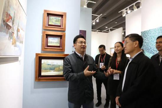 南方财经全媒体集团总经理、南方文交所董事长张志兵为观展领导介绍展位作品。