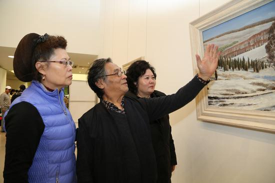 著名画家王昌凯在展览现场欣赏作品