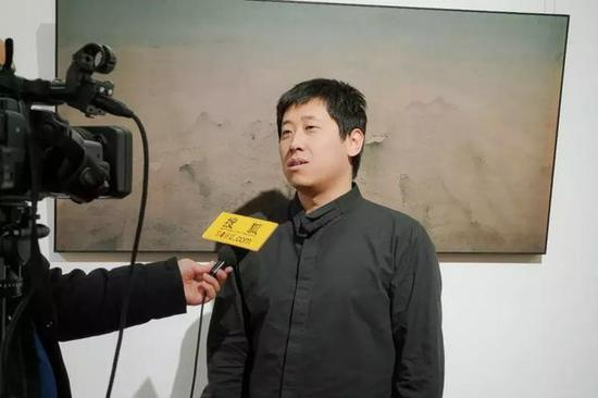 参展艺术家杨新收接受媒体采访