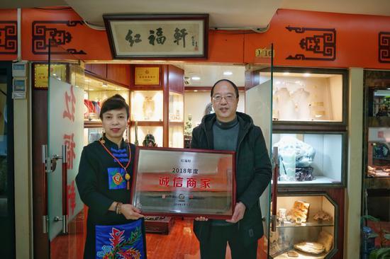 上海市古玩经营协会驻会副会长、宝库汇总经理王承德为红福轩主人翟秀红授牌