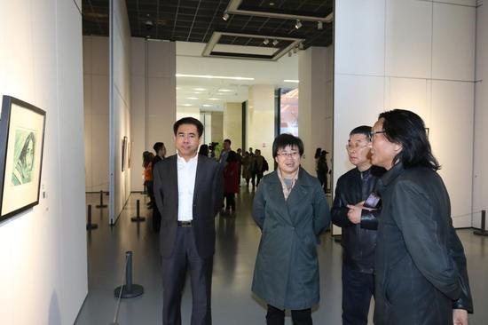 苏新平、贺淑荣、李延春、徐志强在画展现场观看作品。