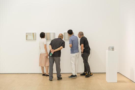 艺术家王豪(右二)、蜂巢执行馆长佟娟娟(左一)陪同艺术家段建伟(左二)及其友人欣赏作品