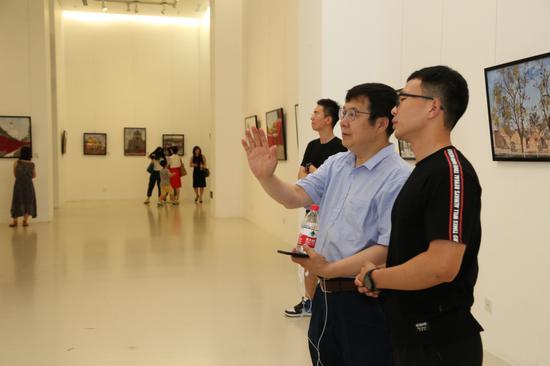 本次展览的画家屈源给嘉宾介绍自己的作品