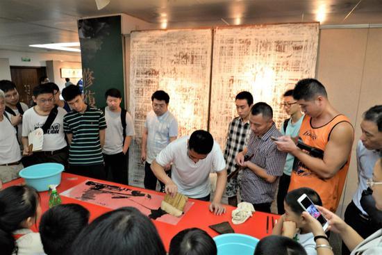 费永明弟子为观众展示古书画修复技术