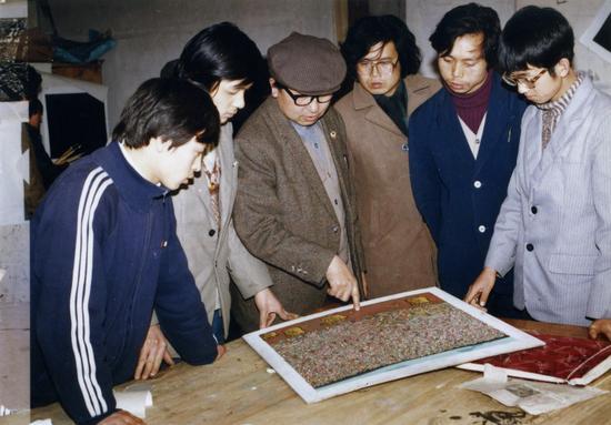 1986年,王训月(左三)与沈少民(左四)为张鹏野(左二)指导版画作品。
