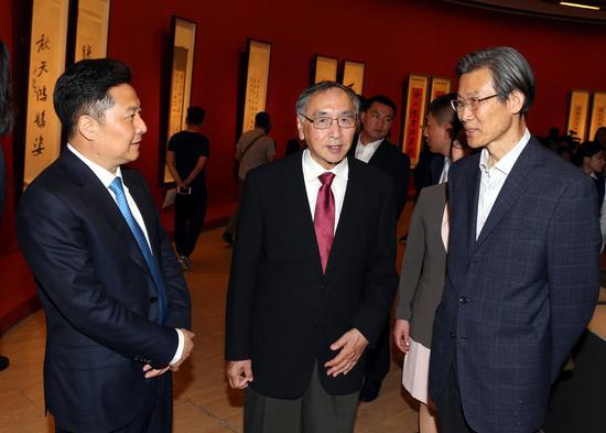 朱奕龙(左一)与于中令(中)在展览现场就本次展览热烈交流
