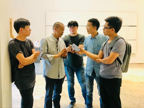艺术家何云昌(左二)接受媒体采访