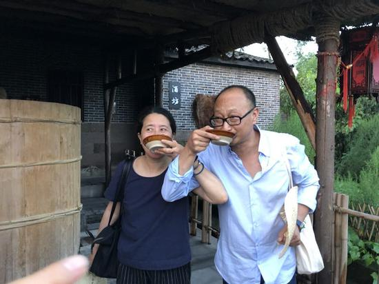 艺术家尹秀珍与策展人冯博一品尝村民酿的粮食酒