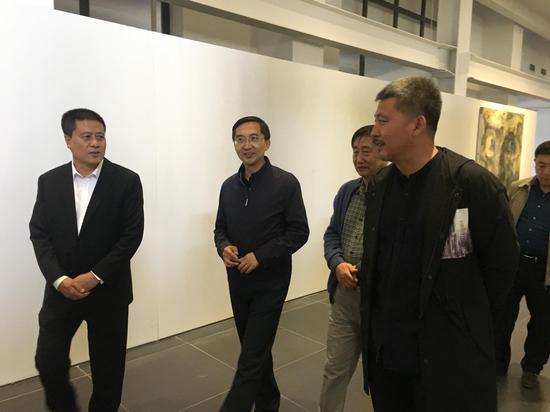 开幕式后艺术家和来宾边观赏作品边进行交流