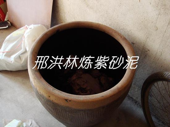 七、把吸收了一些水分的泥用木锤拍打成块,放入缸里,密封一段时间,让其陈腐后,即可用于制壶
