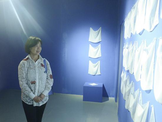 """""""重构当代""""展览现场,展览出品人、上海明圆美术馆馆长凌菲菲在欣赏艺术家陈妍音的装置作品《薄膜》"""