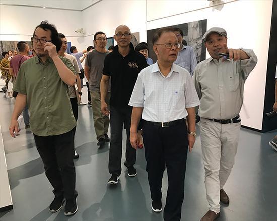 展览会现场,原上海市人大委员会主任、上海视觉艺术学院老校长龚学平(中)参观展览。左起:陈耀明、吴晨荣、龚学平、许德民。