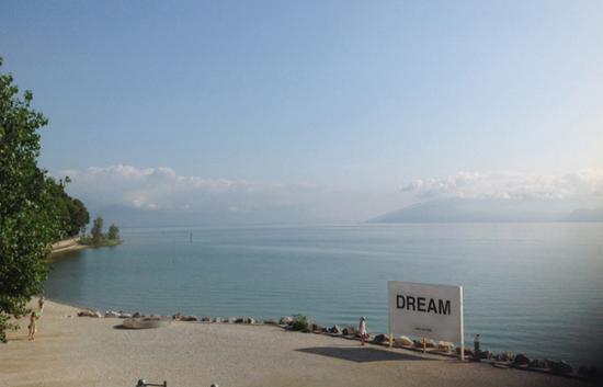 """小野洋子,《只语篇》,""""梦想"""" 1964/2015 (横幅、LED屏幕、海报2015锡尔苗内海滩展览现场图片,意大利加尔达湖 图片由路易吉·博诺托提供)"""