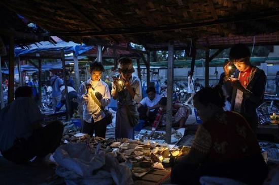 曼德勒,缅甸商人在市场上检查玉器。资料图片