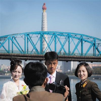 平壤,市民在江边拍婚纱照。