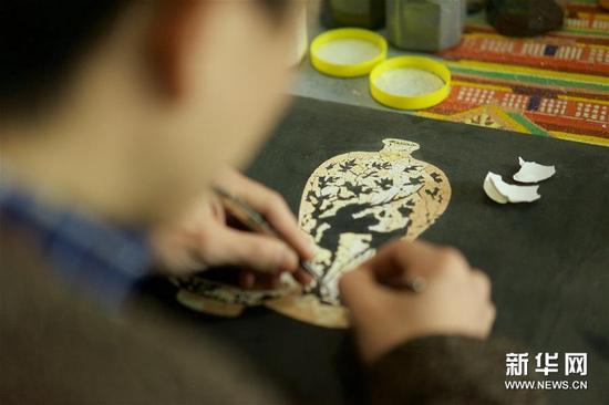 1月15日,胡伟在工作室用蛋壳拼制花瓶。