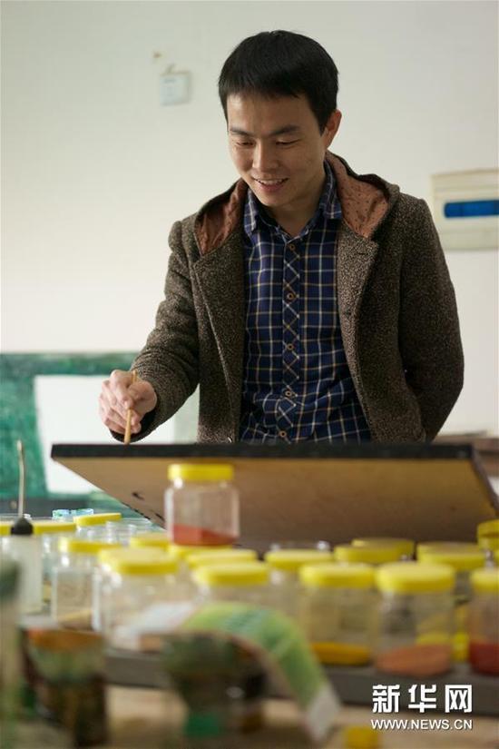 1月15日,胡伟在工作室绘制漆画。
