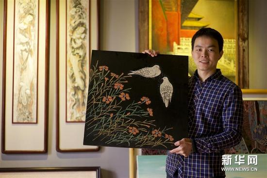 1月15日,胡伟在工作室展示自己的作品。
