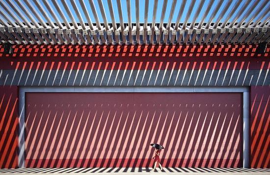 手机组冠军:中国摄影师王建拍摄了这张图片,图中是一位走在红色墙壁前的红衣女子。