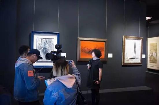 媒体在中国二十世纪及当代艺术展场进行采访,背景为本次春拍吴大羽、赵无极、吴冠中经典力作