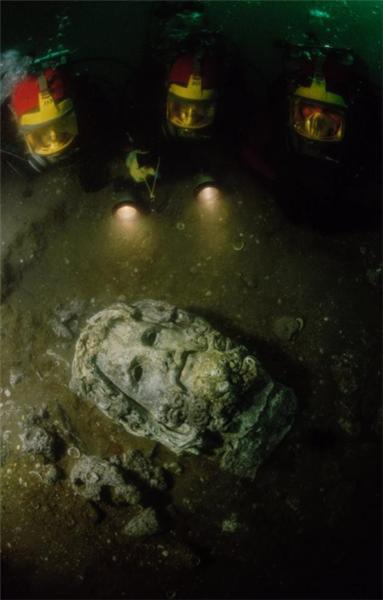 一座雕像正被潜水员挖掘出来