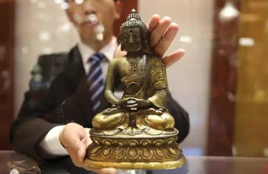 """刘旸介绍,当下市场,佛像收藏比较热门,此次拍卖推出的""""清乾隆铜鎏金无量寿佛像""""尤其突出,同样值得关注"""