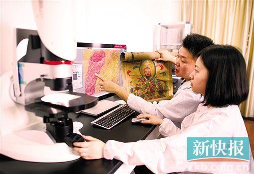 赵晓龙与妻子张晓珑利用显微镜对文物的成分进行分析。新华社发