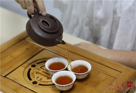 将茶汤注入茶杯之中