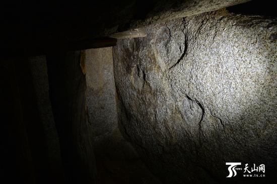 石壁上有红色的石绘,图案是菱形的格子纹,格子中间还有红色的点