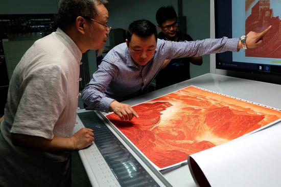 印刷负责人向《万里长城》铜版画作者许仁龙介绍初步上色的画面效果