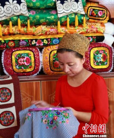 热娜古丽·素批6岁开始就跟母亲学习刺绣技艺,2013年6月,她发起成立了刺绣合作社,开始带徒弟,带动周围的家庭妇女一起致富。 王昊鹏 摄