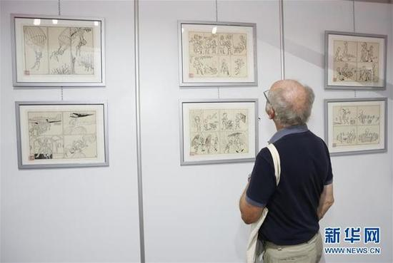 9月3日,在比利时布鲁塞尔,一名参观者在漫画节上欣赏中国展台的漫画插图《三毛》。