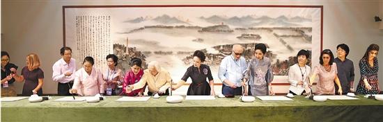 """彭丽媛邀请来宾们一起书写汉字""""和""""。新华社发"""