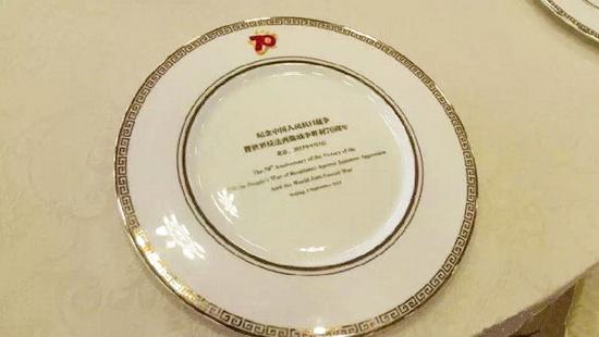 """瓷盘上写着""""纪念中国人民抗日战争暨世界反法西斯战争胜利70周年 北京:2015年9月3日"""",并打上了此次纪念活动的LOGO"""
