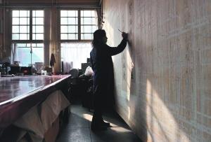 故宫博物院文物保护技术人员在对古书画进行全色。新华社资料图