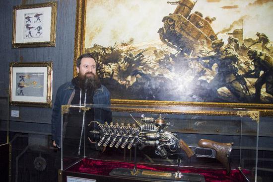 《格特博士的世界》作者设计师葛雷格与他最喜欢的武器(模型)合影