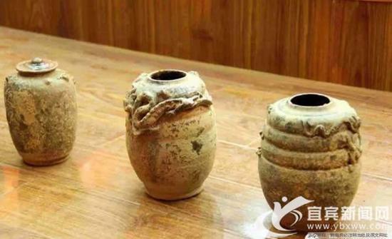 陶罐表面有龙纹浮雕。(伍鸥 摄)