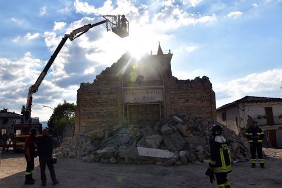 意大利地震发生后,部分救援人员来到教堂查看文物的损毁情况。