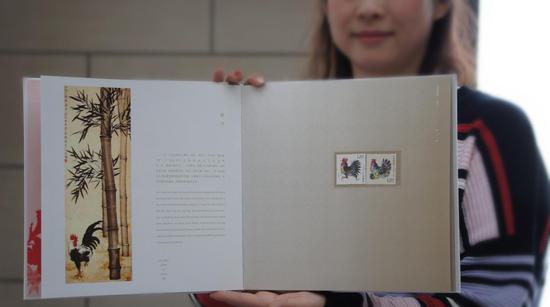 工作人员展示《金鸡报晓》生肖文化专题册