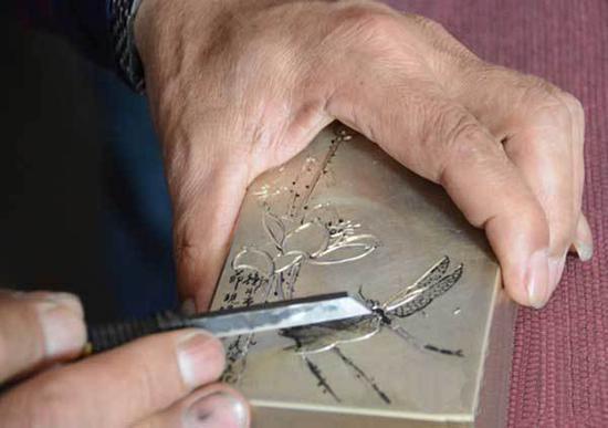 宋国柱的刻刀在铜面上挥洒自如(长城网供图)