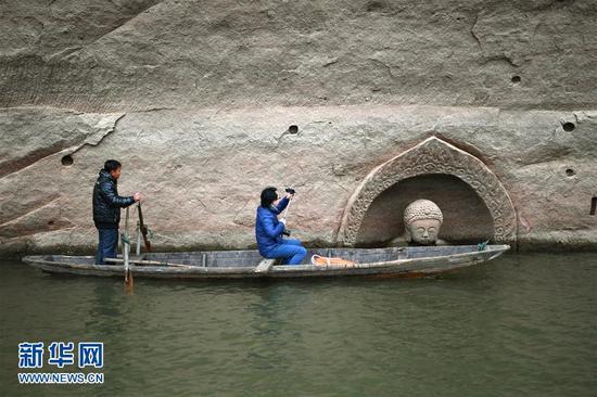 考古人员在对露出水面的佛头进行拍摄