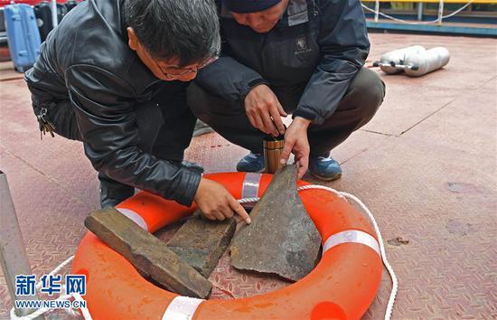 考古人员在观察打捞上来的物品