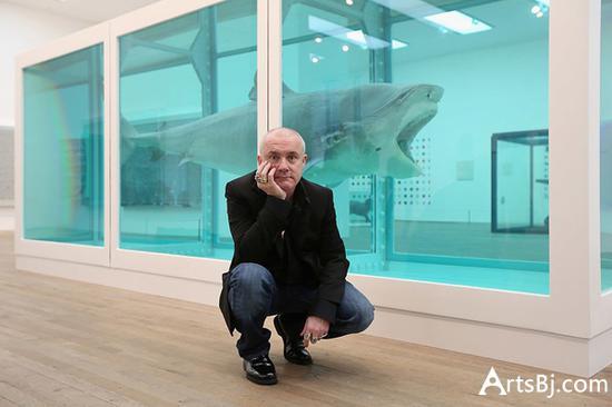 2012年在泰特美术馆,达明·赫斯特在作品前合影。图片:Photo by Oli Scarff Getty Images.