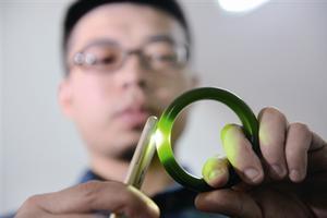工作人员利用手机的手电灯光照着看产品内部结构,产品中有气泡即可判定是玻璃。